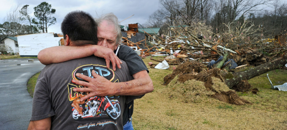 Greg Cook hugs his friend David Derrick at East Limestone community on Friday, March 2, 2012.  A reported tornado destroyed several houses in northern Alabama as storms threatened more twisters across the region Friday (AP Photo/The Decatur Daily, Gary Cosby Jr.) ORG XMIT: ALDEC103