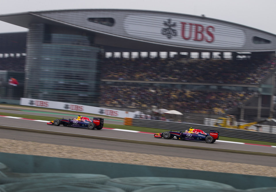 Photo - Red Bull Racing driver Sebastian Vettel of Germany, left, and his teammate Daniel Ricciardo of Australia drive past the grand stand during the Chinese Formula One Grand Prix at Shanghai International Circuit in Shanghai, China Sunday, April 20, 2014. (AP Photo/Andy Wong)