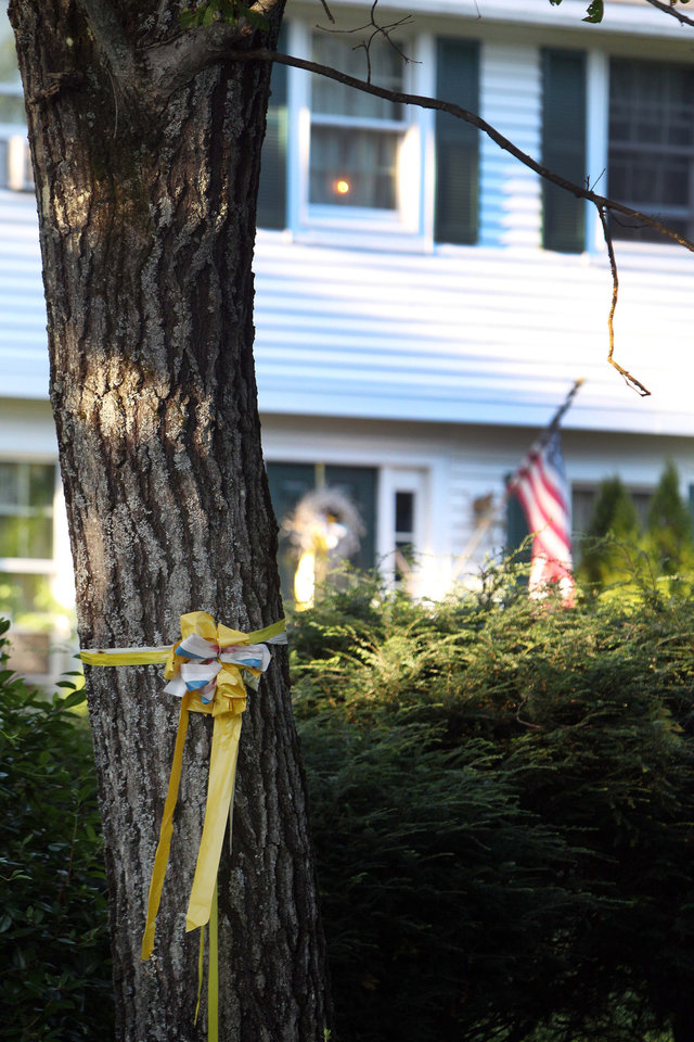 Photo - A ribbon is tied to a tree outside the home of American freelance journalist James Foley, on Tuesday Aug. 19, 2014, in Rochester, N.H. A video by Islamic State militants that purports to show the killing of Foley by the militant group was released Tuesday. (AP Photo/Jim Cole)