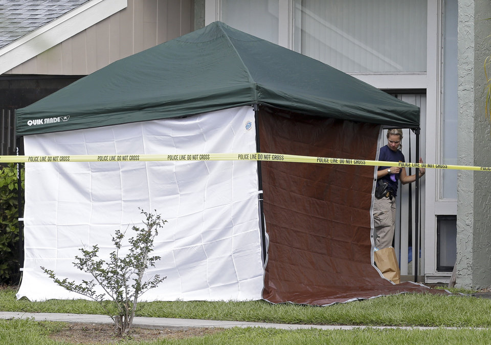 Photo - An FBI investigator enters the apartment  where a man was shot by an FBI agent, Wednesday, May 22, 2013, in Orlando, Fla. The FBI says the man, being questioned by authorities in the Boston bombing probe, was fatally shot when he initiated a violent confrontation. (AP Photo/John Raoux)