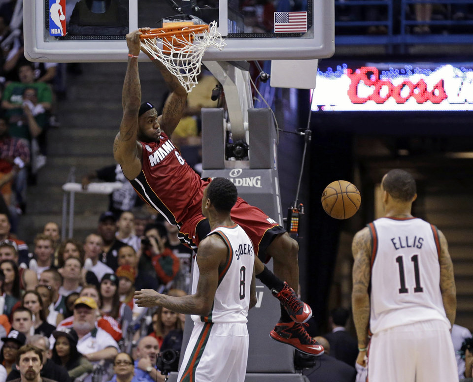 Miami Heat\'s LeBron James (6) dunks as Milwaukee Bucks\' Larry Sanders (8) and Monta Ellis watch during the second half of Game 4 in their first-round NBA basketball playoff series, Sunday, April. 28, 2013, in Milwaukee. Miami won 88-77. James scored 30 points. (AP Photo/Jeffrey Phelps)