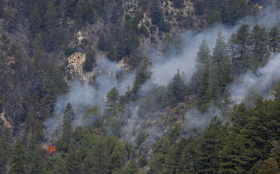 Photo - A smaller fire burns near the Slide Fire as it burns up Oak Creek Canyon on Friday, May 23, 2014, near Flagstaff, Ariz.  The fire has burned approximately 7,500 acres and is five percent contained. (AP Photo/Ross D. Franklin)