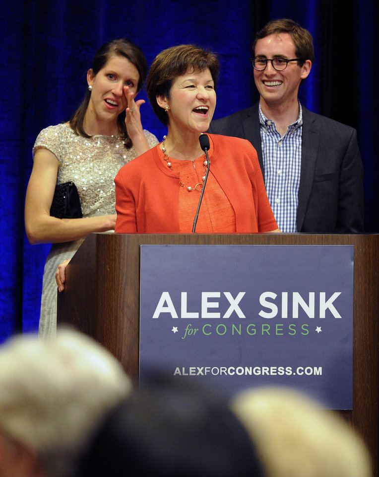 Photo - Congressional candidate Alex Sink gives her concession speech as she is flanked by her daughter Lexi Crawford and Lexi's husband, Douglas, Tuesday, March 11, 2014, in St. Petersburg, Fla. Sink ran against Republican David Jolly to fill the vacant District 13 seat after the death of C.W. Bill Young. (AP Photo/The Tampa Tribune, Chris Urso)  ST. PETERSBURG OUT; LAKELAND OUT; BRADENTON OUT; MAGS OUT; LOCAL TV OUT; WTSP CH 10 OUT; WFTS CH 28 OUT; WTVT CH 13 OUT; BAYNEWS 9 OUT; THE TAMPA BAY TIMES OUT; LAKELAND LEDGER OUT; BRADENTON HERALD OUT; SARASOTA HERALD-TRIBUNE OUT; WINTER HAVEN NEWS CHIEF OUT