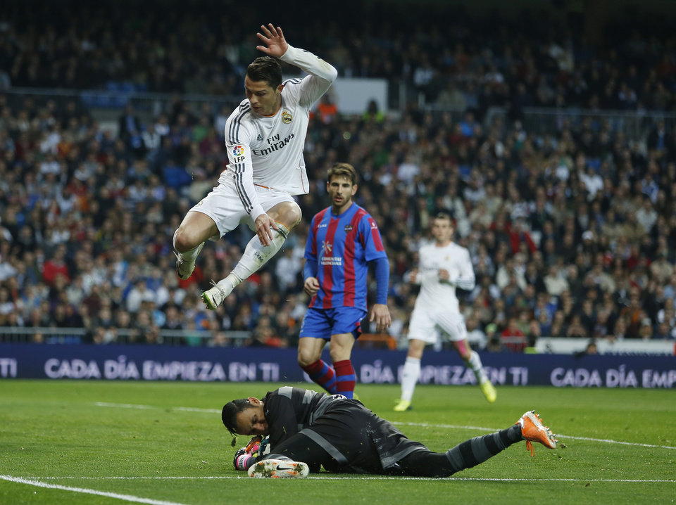 Photo - Real's Cristiano Ronaldo, top, in action Levante's goalkeeper Keylor Navas, bottom, during a Spanish La Liga soccer match between Real Madrid and Levante at the Santiago Bernabeu stadium in Madrid, Spain, Sunday, March 9, 2014. (AP Photo/Andres Kudacki)
