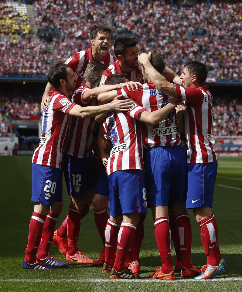 Photo - Atletico's Raul Garcia, second left, partly seen, celebrates his goal with teammates during a Spanish La Liga soccer match between Atletico Madrid and  Villarreal at the Vicente Calderon stadium in Madrid, Spain, Saturday, April 5, 2014. (AP Photo/Andres Kudacki)