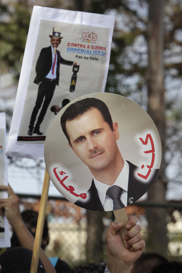 Photo - A demonstrator holds up a picture of Syria's President Bashar Assad in front of a poster of a defaced image of President Barack Obama that reads in Portuguese