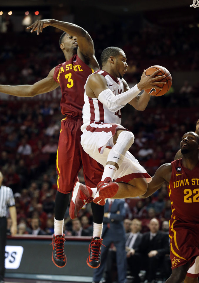 Photo - Oklahoma Sooner's Jordan Woodard (10) looks to pass after driving past Iowa State Cyclone's Melvin Ejim (3) as the University of Oklahoma Sooners (OU) men defeat the Iowa State Cyclones (ISU) 87-82 in NCAA, college basketball at The Lloyd Noble Center on Saturday, Jan. 11, 2014  in Norman, Okla. Photo by Steve Sisney, The Oklahoman