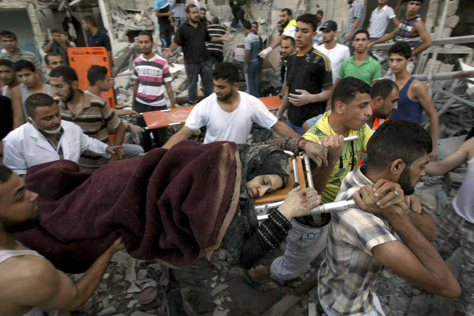 Photo - Palestinians evacuate a survivor of an Israeli air strike that hit the Al Ghoul family building in Rafah, southern Gaza Strip, Sunday, Aug. 3, 2014. At least 40 people were inside the Al Ghoul family building in the Rafah when it was targeted by Israeli jet fighters, according to the Red Crescent and Gaza health official Ashraf al-Kidra. Many have been confirmed dead and over two dozen have been wounded. (AP Photo/Eyad Baba)
