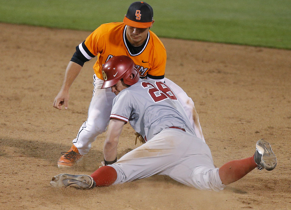 Photo - OSU's Tim Arakawa tags out OU's Mac James at second base in the 15th inning of a Bedlam baseball game between Oklahoma State University and the University of Oklahoma in Stillwater, Tuesday, April 15, 2014. Photo by Bryan Terry, The Oklahoman