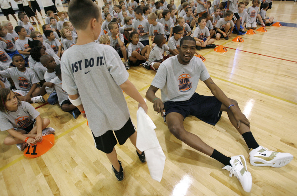 Photo - Kevin Durant hands a signed T-shirt to Noah Kern, 9 of Muskogee after a shootout during the second day of the Kevin Durant basketball camp at Heritage Hall in Oklahoma City, Thursday, June 30, 2011.  Photo by Garett Fisbeck, The Oklahoman