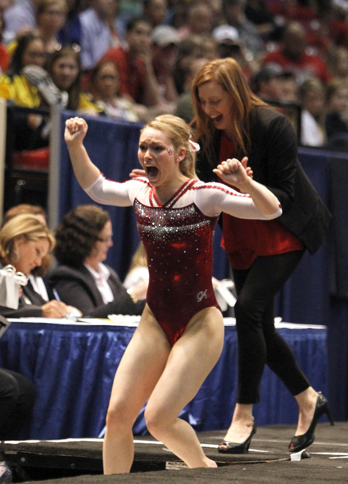 Photo - Oklahoma's Haley Scaman, foreground, celebrates with coach KJ Kindler after her vault routine during the NCAA college women's gymnastics championships on Saturday, April 19, 2014, in Birmingham, Ala. (AP Photo/Butch Dill)