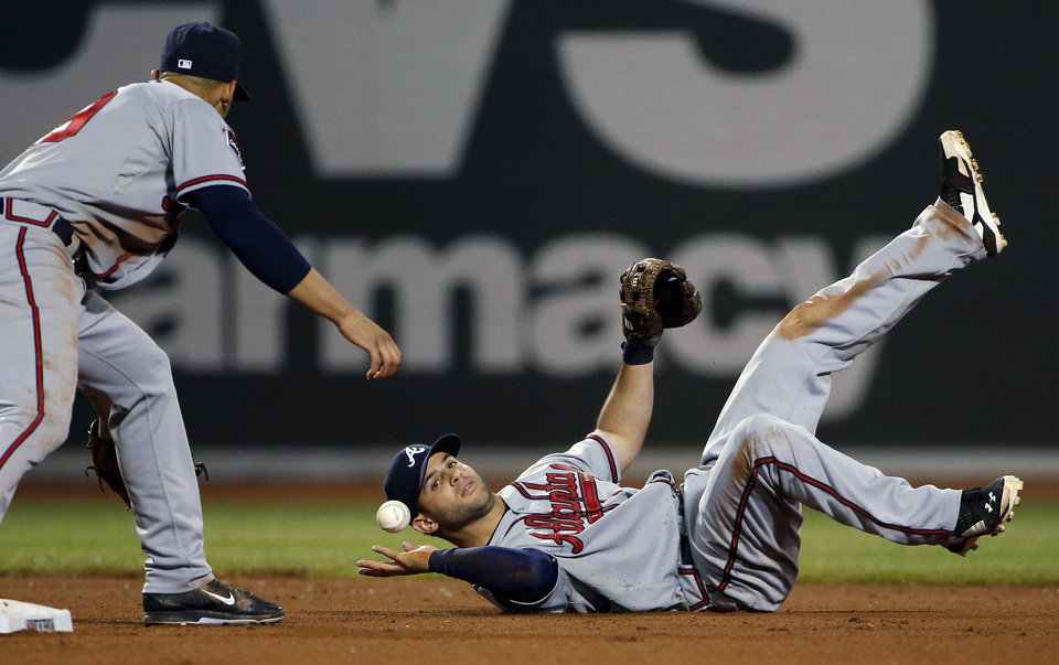 Photo - Atlanta Braves second baseman Tommy La Stella bobbles an infield hit by Boston Red Sox's Dustin Pedroia as shortstop Andrelton Simmons waits at second base for the ball during the eighth inning of a baseball game at Fenway Park in Boston, Thursday, May 29, 2014. (AP Photo/Winslow Townson)