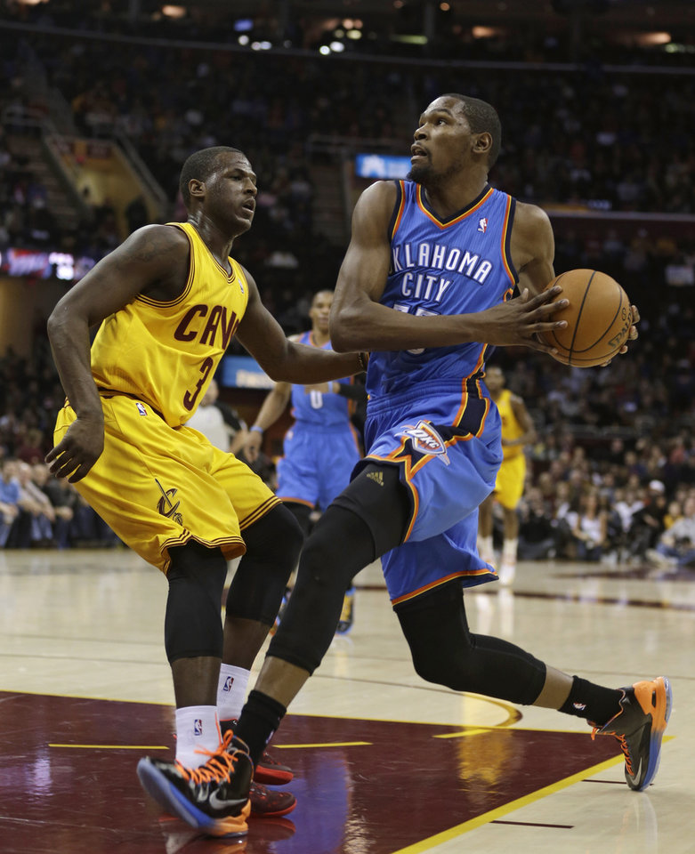 Photo - Oklahoma City Thunder's Kevin Durant, right, drives to the basket against Cleveland Cavaliers' Dion Waiters during the first quarter of an NBA basketball game on Saturday, Feb. 2, 2013, in Cleveland. (AP Photo/Tony Dejak) ORG XMIT: OHTD101