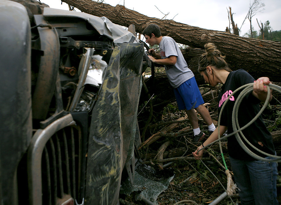 Photo - Caden Bolles and his girlfriend Mary Reed (right) collect Caden's belongings from his truck at his family's home in Little Axe, Oklahoma on Tuesday, May 11, 2010. By John Clanton, The Oklahoman