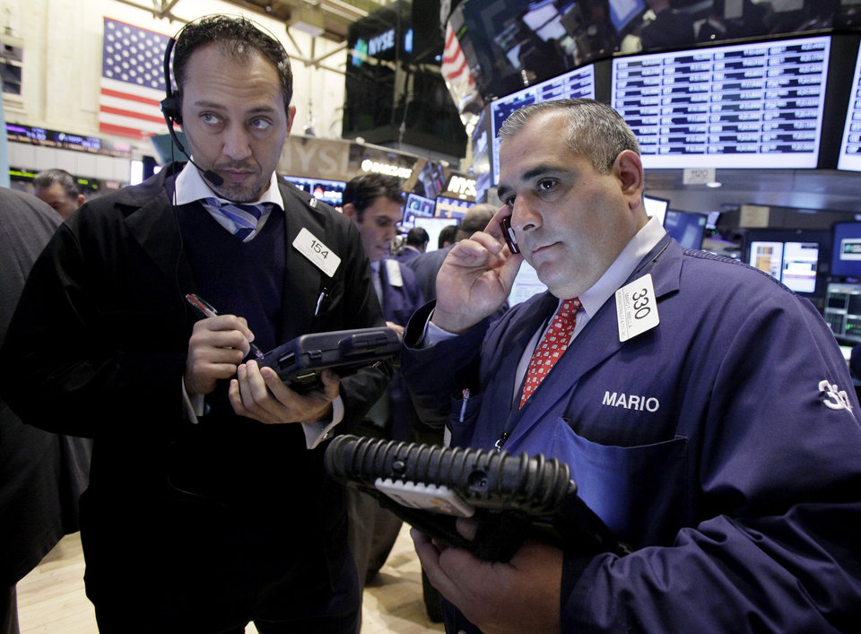 Photo - Traders Fady Tanios, left, and Mario Innella work on the floor of the New York Stock Exchange Tuesday, Dec. 11, 2012. Stocks opened higher Tuesday ahead of a meeting of the Federal Reserve and possible additional steps to bolster the U.S. economy.  (AP Photo/Richard Drew)