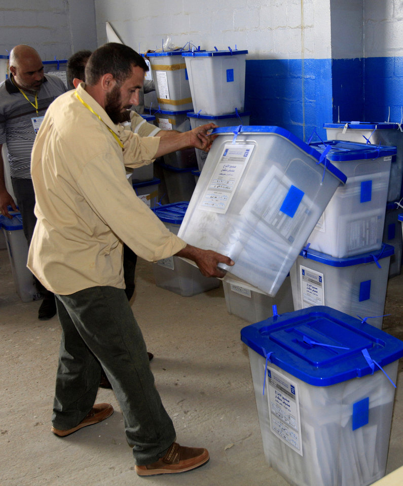 Photo - Electoral workers inspect ballot boxes at a counting center in Baghdad, Iraq, Sunday, April 21, 2013. Iraqis have begun counting votes from the first provincial elections since the last U.S. troops withdrew in December 2011. (AP Photo/ Karim Kadim)