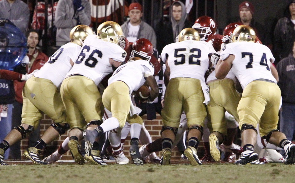Photo -   Notre Dame quarterback Everett Golson, center, dives in for a touchdown against Oklahoma during the fourth quarter of an NCAA college football game in Norman, Okla., Saturday, Oct. 27, 2012. Notre Dame won 30-13. (AP Photo/Alonzo Adams)