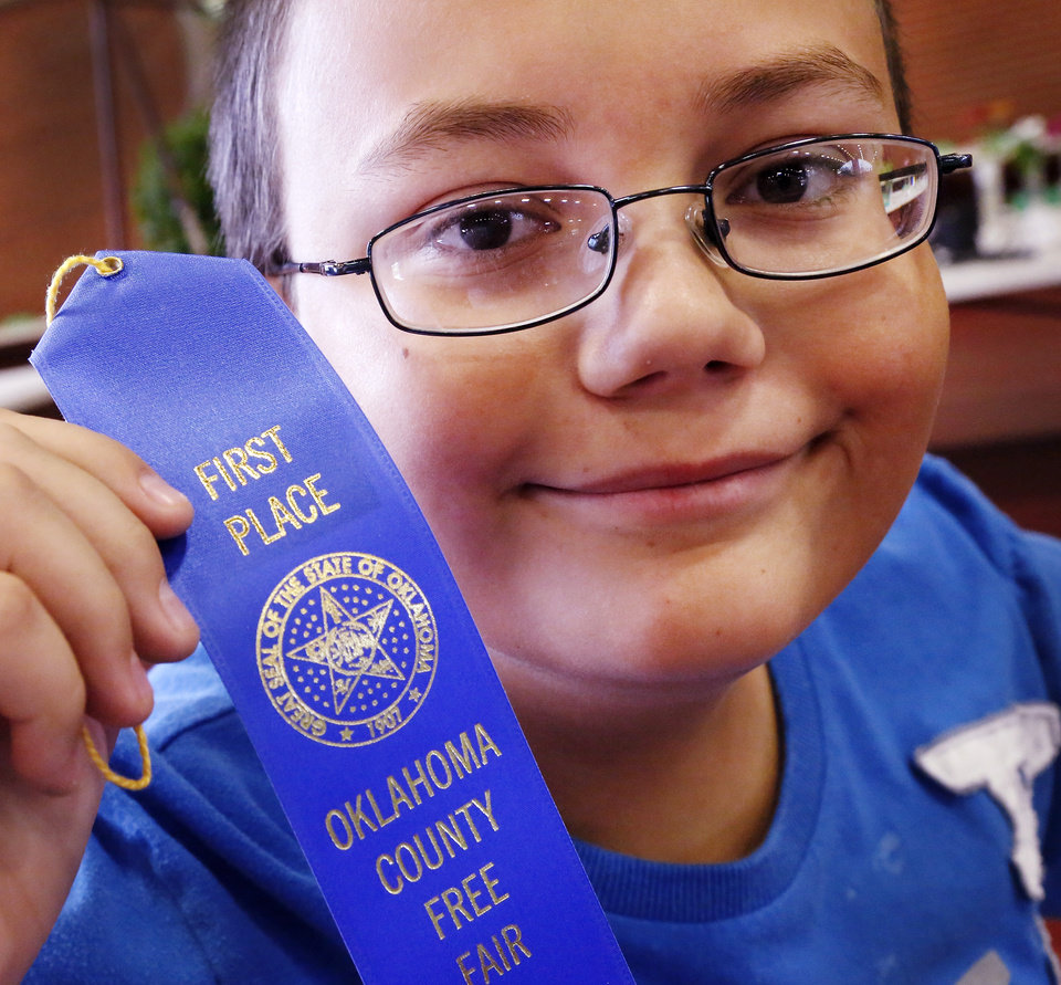 Photo -  William Blasius, 12, displays his first-place blue ribbon at the Oklahoma County Free Fair. Photo by Jim Beckel, The Oklahoman   Jim Beckel -