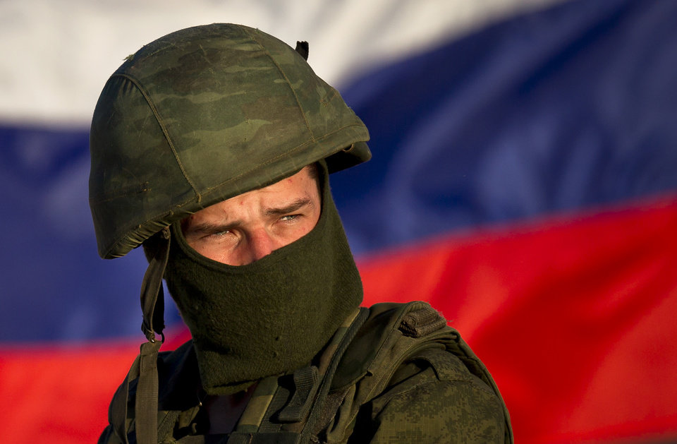 Photo - A pro-Russian soldier is back dropped by Russia's flag while manning a machine-gun outside an Ukrainian military base in Perevalne, Ukraine, Saturday, March 15, 2014. Tensions are high in the Black Sea peninsula of Crimea, where a referendum is to be held Sunday on whether to split off from Ukraine and seek annexation by Russia.(AP Photo/Vadim Ghirda)