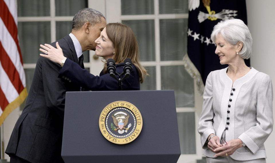 Photo - President Barack Obama hugs his nominee to become Health and Human Services Secretary, current Budget Director Sylvia Mathews Burwell as outgoing HHS Secretary Kathleen Sebelius watches at right, Friday, April 11, 2014, in the Rose Garden of the White House in Washington, where the president made the announcement. (AP Photo/Susan Walsh)