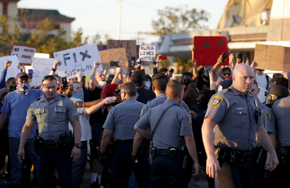 Photo - Police stand in front of protesters during a protest near the intersection of 23rd and Classen in Oklahoma City, Saturday, May 30, 2020. The protest was in response to the death of George Floyd. [Sarah Phipps/The Oklahoman]