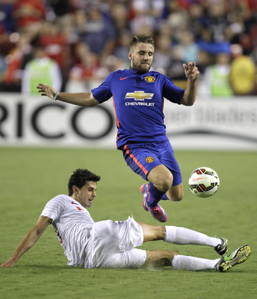 Photo - Manchester United's Luke Shaw jumps over Inter Milan's Andrea Ranocchia during the second half of  the 2014 Guinness International Champions Cup soccer game, Tuesday, July 29, 2014, in Landover, Md. Manchester United won 5-3 in a penalty kick shootout. (AP Photo/Luis M. Alvarez)