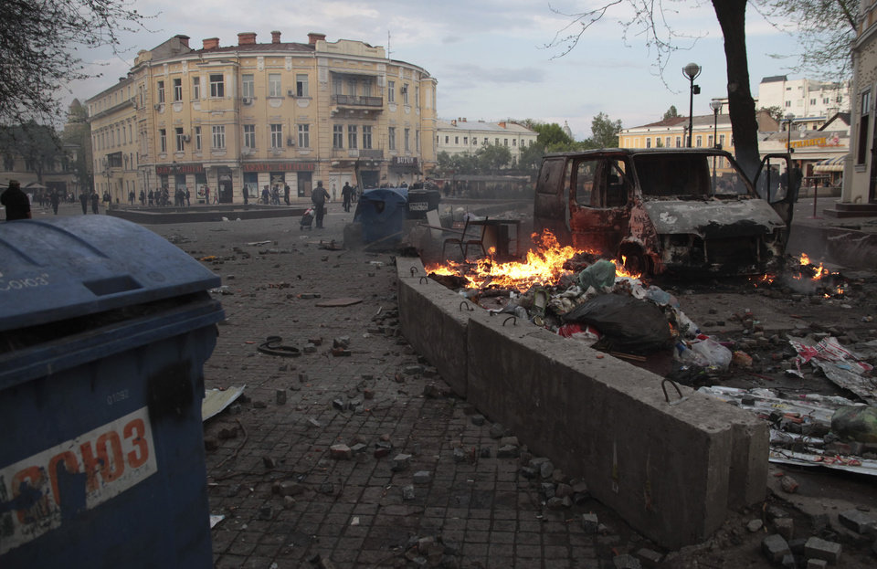 Photo - Trashed items are smoldering among debris at a square following clashes in Odessa, Ukraine, on Friday, May 2, 2014. Odessa had been largely tranquil since the February toppling of President Viktor Yanukovych, who fled to Russia. But clashes erupted Friday between pro-Russians and government supporters in the key port on the Black Sea coast, located 550 kilometers (330 miles) from the turmoil in the east. (AP Photo/Sergei Poliakov)