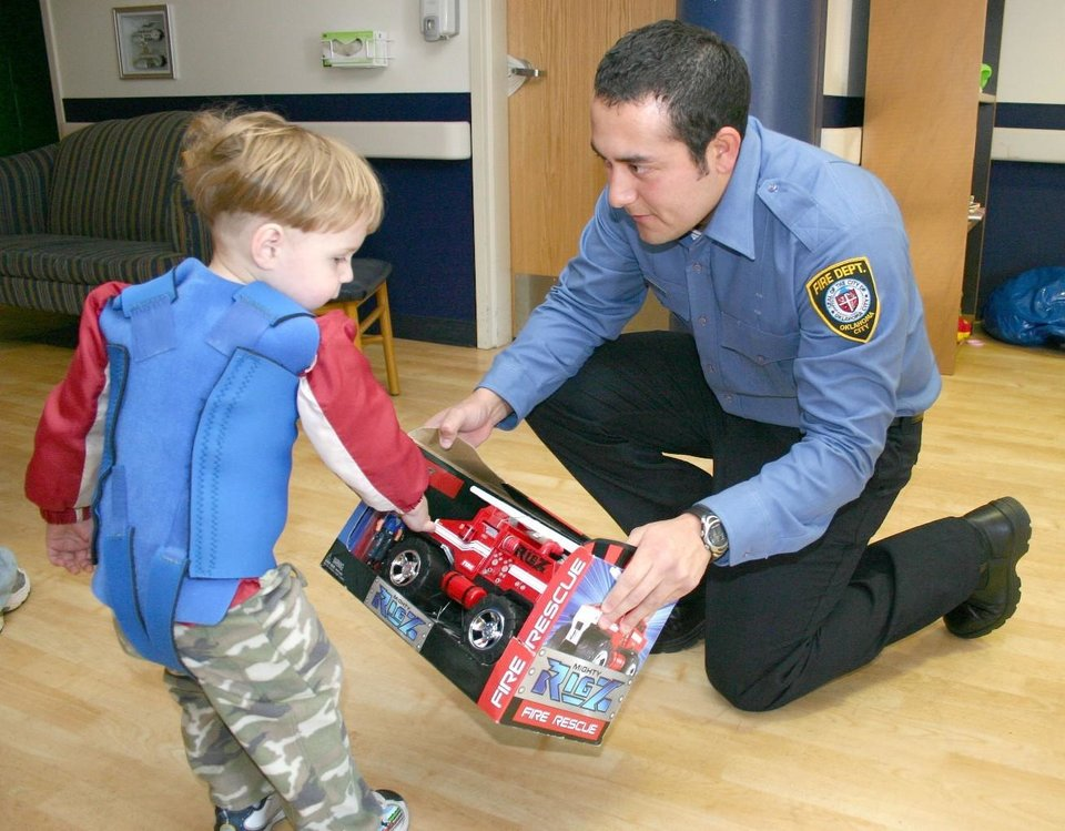 Oklahoma City Fire Department recruit Tony Sousa, age 26, offers a fire rescue truck to J. D. McCarty Center patient Jeramy Joyner, age 3, from Pauls Valley, Oklahoma. Sousa was one of eight fire department recruits representing the 50 members of recruit class 071 who answered the call for assistance by acquiring and delivering games, toys and sports equipment to the McCarty Center. Community Photo By: Greg Gaston Submitted By: Greg, Norman
