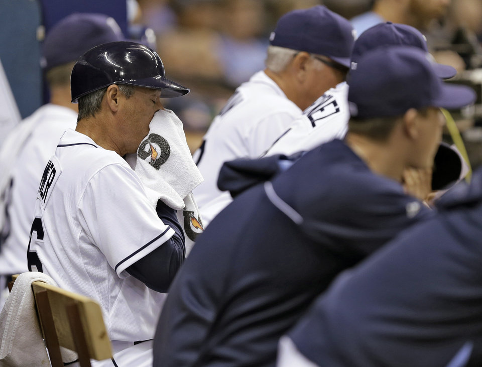 Photo - Tampa Bay Rays third base coach Tom Foley wipes his face after word spread through the Rays dugout that team special advisor Don Zimmer had passed away.  The Rays were playing the Miami Marlins during an interleague baseball game Wednesday, June 4, 2014, in St. Petersburg, Fla. (AP Photo/Chris O'Meara)