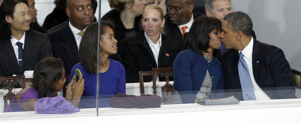 Photo - President Barack Obama kisses first lady Michelle Obama as their daughters Sasha, left, and Malia, second from left, look on during the Inaugural parade, Monday, Jan. 21, 2013, in Washington. Thousands  marched during the 57th Presidential Inauguration parade after the ceremonial swearing-in of President Barack Obama. (AP Photo/Gerald Herbert) ORG XMIT: DCMS135