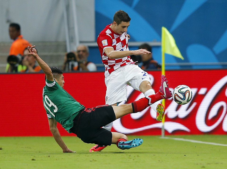 Photo - Mexico's Oribe Peralta, left, fights for the ball with Croatia's Sime Vrsaljko during the group A World Cup soccer match between Croatia and Mexico at the Arena Pernambuco in Recife, Brazil, Monday, June 23, 2014. (AP Photo/Eduardo Verdugo)