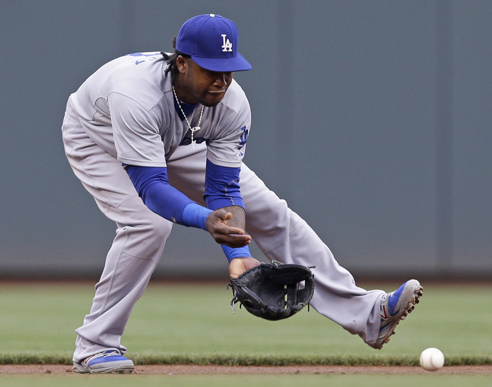 Photo - Los Angeles Dodgers shortstop Hanley Ramirez fields a ground ball hit by Cincinnati Reds' Brandon Phillips in the first inning of a baseball game, Monday, June 9, 2014, in Cincinnati. Ramirez threw Phillips out at first. (AP Photo/Al Behrman)