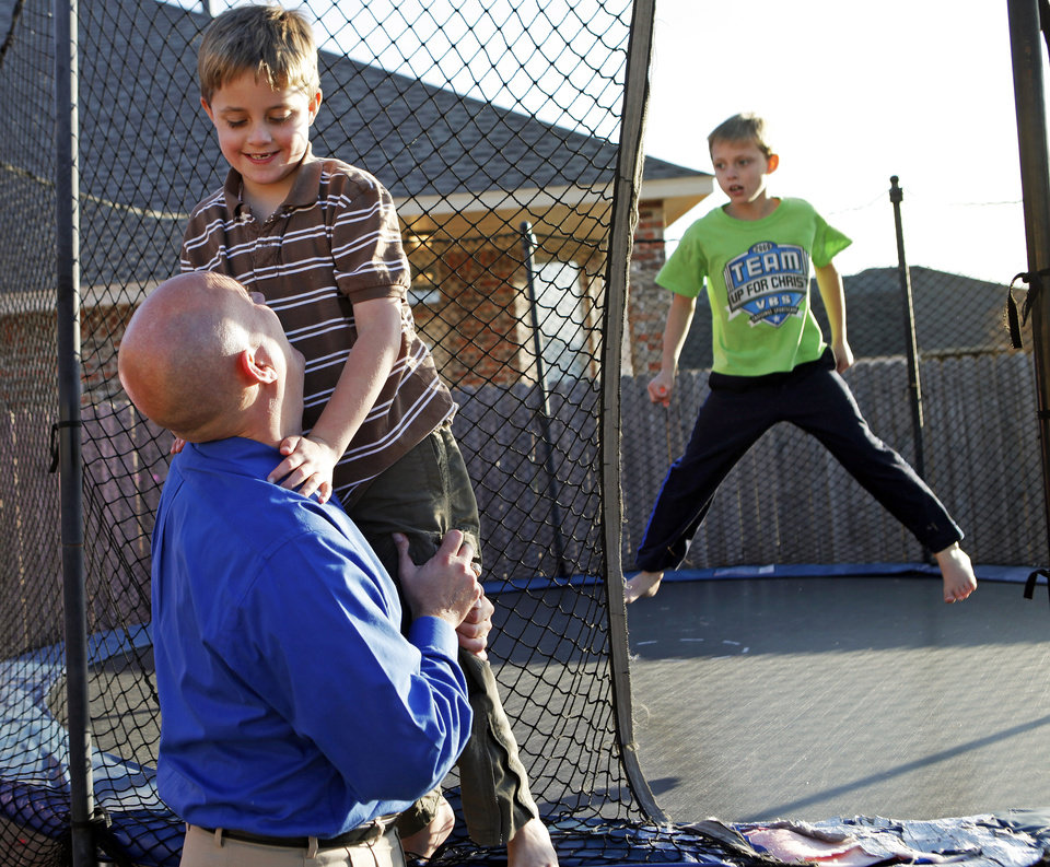 Eric Littleton, left, holds son Solomon Littleton, 7, as Solomon's twin brother Isaac Littleton jumps on a trampoline at their home, 17313 Zinc Drive, in Edmond, Okla., Thursday, December 16, 2010. Solomon Littleton has a neurological disorder that gives him symptoms similar to autism and Alzheimer's disease. Photo by Nate Billings, The Oklahoman