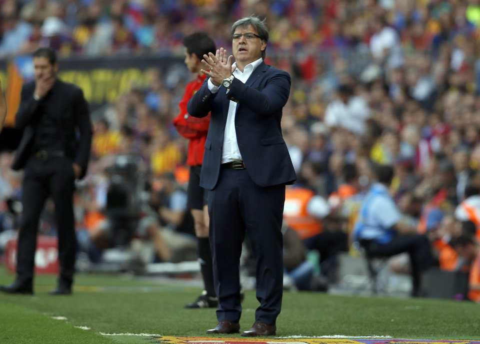 Photo - Barcelona's coach Gerardo Martino from Argentina applauds during a Spanish La Liga soccer match between FC Barcelona and Atletico Madrid at the Camp Nou stadium in Barcelona, Spain, Saturday, May 17, 2014. (AP Photo/Emilio Morenatti)