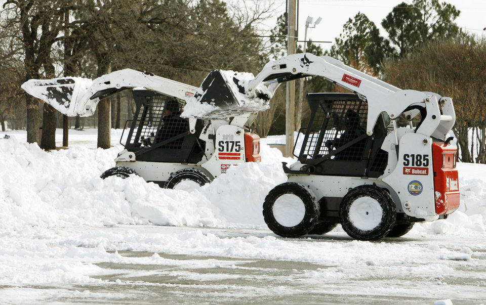 Photo - Bobcats clear snow from the parking lot at the Oklahoma City Zoo in Oklahoma City, OK, Thursday, Feb. 3, 2011. By Paul Hellstern, The Oklahoman