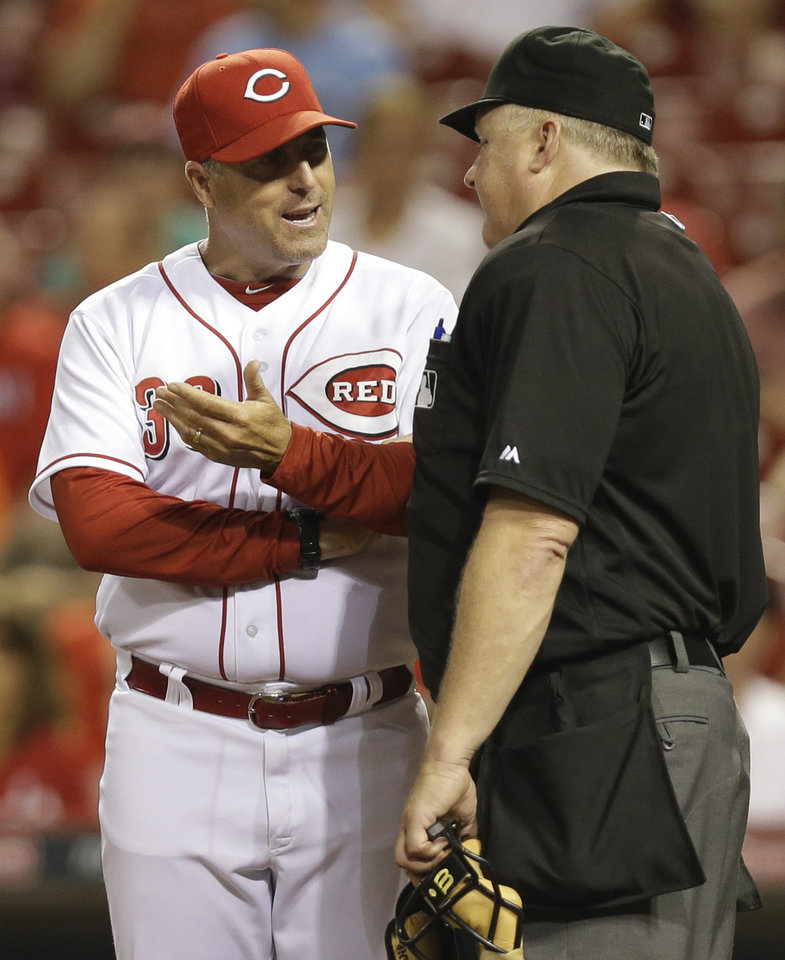 Photo - Cincinnati Reds manager Bryan Price (38) argues a called third strike against Kris Negron with home plate umpire Bill Miller in the fifth inning of a baseball game against the Chicago Cubs, Tuesday, Aug. 26, 2014, in Cincinnati. (AP Photo/Al Behrman)