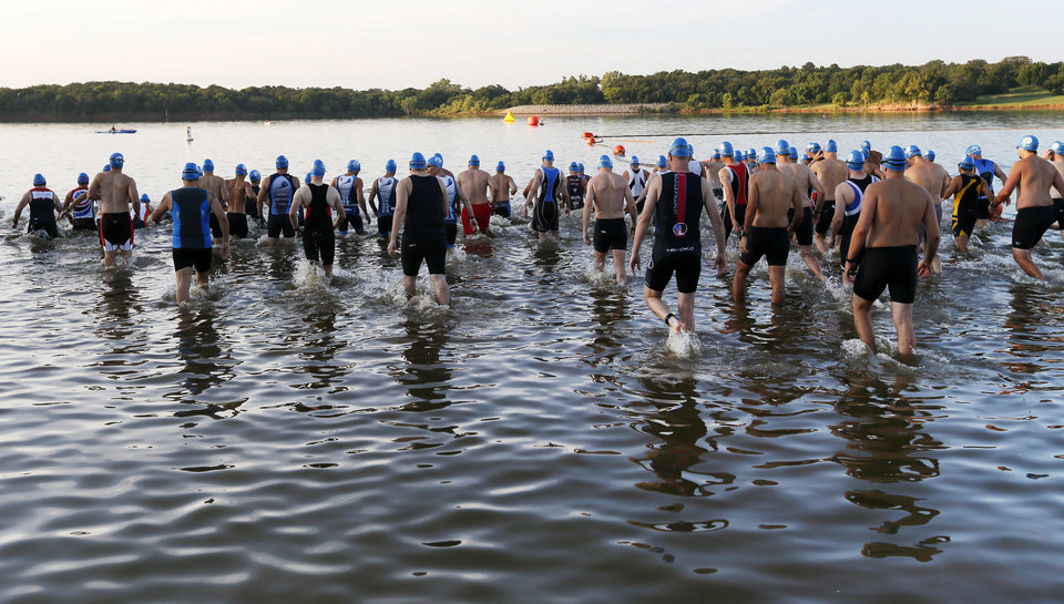 Photo -  Swimmers wade into the water before the Arcadia Lake Triathlon and Aquabike at Edmond Park. PHOTO BY NATE BILLINGS, THE OKLAHOMAN   NATE BILLINGS -
