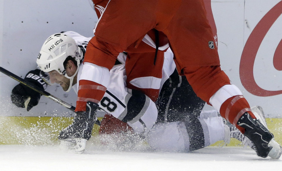 Photo - Los Angeles Kings center Jarret Stoll (28) is checked by Detroit Red Wings right wing Luke Glendening during the first period of an NHL hockey game in Detroit, Saturday, Jan. 18, 2014. (AP Photo/Carlos Osorio)