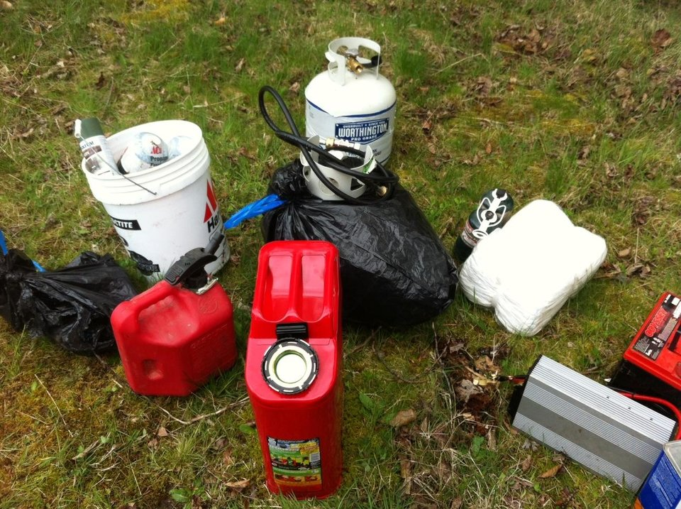 Photo -   In this photo provided by the King Co. Sheriff's Dept., fuel containers and other items that were found in a deep-woods bunker, Saturday, April 28, 2012, near North Bend, Wash. are displayed after they were removed by deputies. Officials also found a body in the bunker that is believed to be Peter A. Keller, who is suspected of hiding out in the bunker after killing his wife and daughter last week. (AP Photo/King Co. Sheriff's Dept.)