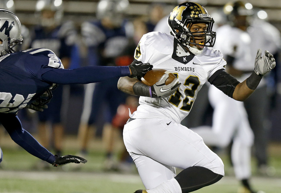 Photo - Midwest City's Cornell Neal runs past Edmond North's Dante Sanders during their high school football game at Wantland Stadium in Edmond, Thursday, October 25, 2012. Photo by Bryan Terry, The Oklahoman