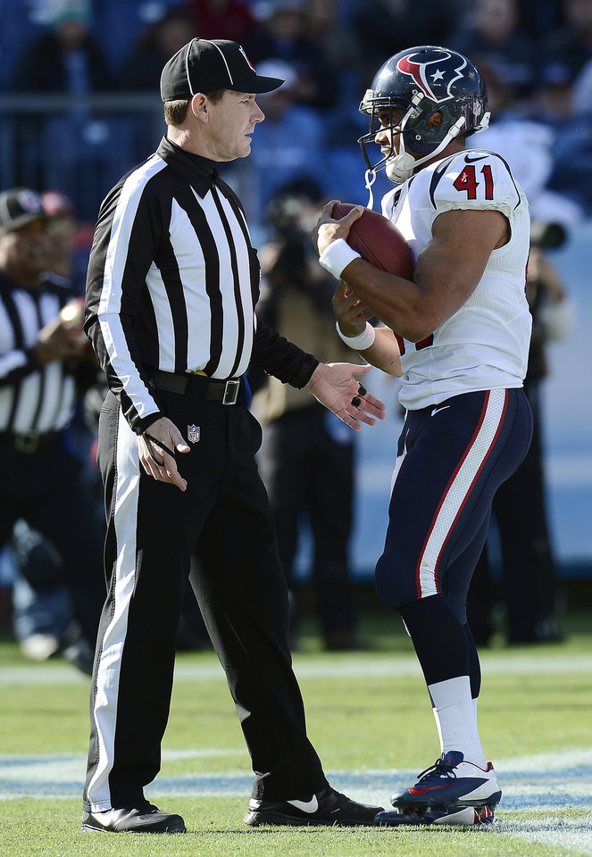 Photo - Houston Texans running back Jonathan Grimes (41) tells back judge Lee Dyer, left, that he wants to keep the football after scoring his first career touchdown on a 3-yard run against the Tennessee Titans in the first quarter of an NFL football game Sunday, Dec. 29, 2013, in Nashville, Tenn. (AP Photo/Mark Zaleski)