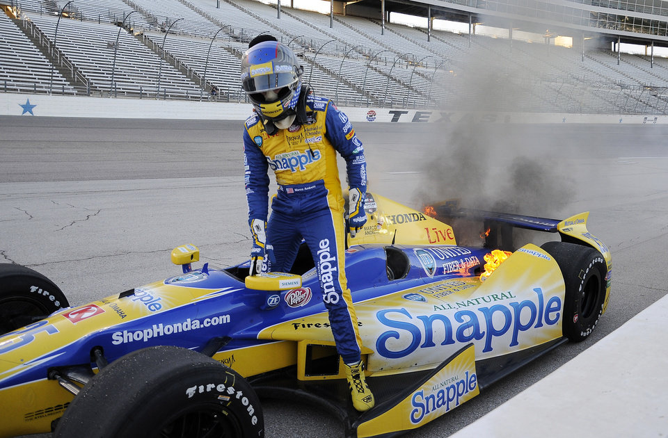 Photo - Marco Andretti gets out of his car on the apron of Turn 4 as flames come from the rear of the car during the IndyCar auto race at Texas Motor Speedway in Fort Worth, Texas, Saturday, June 7, 2014. (AP Photo/Larry Papke)