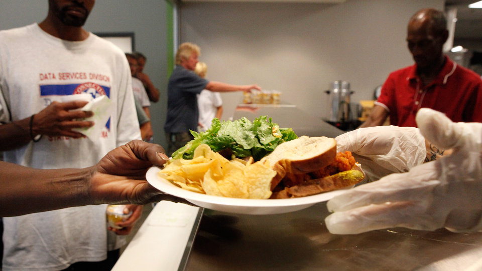A man accepts a plate of food from a server at lunchtime at at the newly opened West Town Homeless Day Shelter and Resource Center at NW 3 and Virginia on Wednesday, Aug. 24, 2011. The Homeless Alliance operates the center.   Photo by Jim Beckel, The Oklahoman