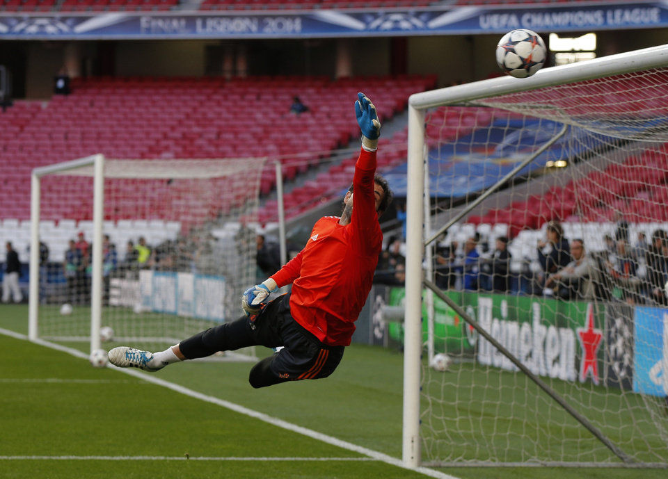 Photo - Real goalkeeper Iker Casillas reaches to stop the ball, during a training session ahead of Saturday's Champions League final soccer match between Real Madrid and Atletico Madrid, in Luz stadium in Lisbon, Portugal, Friday, May 23, 2014. (AP Photo/Daniel Ochoa de Olza)