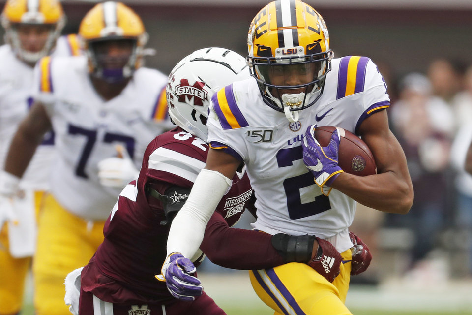 Photo - LSU wide receiver Justin Jefferson (2) tries to fight off a tackle by Mississippi State safety Brian Cole II (32) after a pass reception during the first half of their NCAA college football game in Starkville, Miss., Saturday, Oct. 19, 2019. (AP Photo/Rogelio V. Solis)
