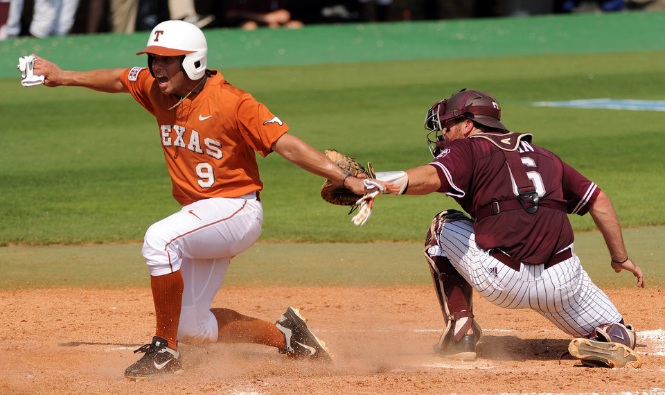 Photo - Texas' C.J. Hinojosa, left, signals himself safe after scoring a run as Texas A&M catcher Troy Stein applies a late tag during the third inning of an NCAA college baseball tournament regional game Friday, May 30, 2014, at Reckling Park in Houston. (AP Photo/Houston Chronicle, Eric Christian Smith) MANDATORY CREDIT