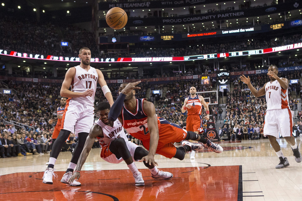 Photo - Washington Wizards' John Wall (2) shoots after being fouled by Toronto Raptors' Amir Johnson (15) during first half NBA basketball action in Toronto, Thursday, Feb. 27, 2014. (AP Photo/The Canadian Press, Chris Young)