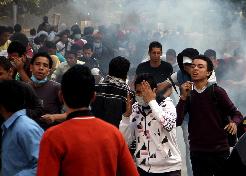 Photo -   Egyptian protesters clash with security forces, not pictured, near Tahrir Square in Cairo, Egypt, Sunday, Nov. 25, 2012. President Mohammed Morsi edicts, which were announced on Thursday, place him above oversight of any kind, including that of the courts. The move has thrown Egypt's already troubled transition to democracy into further turmoil, sparking angry protests across the country to demand the decrees be immediately rescinded. (AP Photo/Ahmed Gomaa)