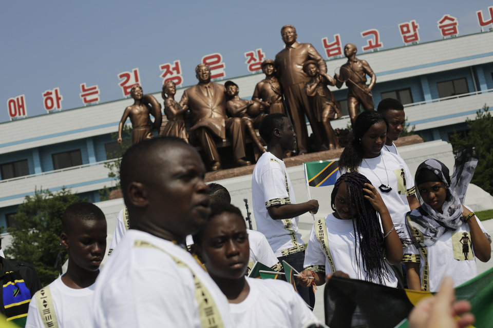 Photo - Students from the Laureat International School in Tanzania walk past a statue of the late North Korean leaders Kim Il Sung and Kim Jong Il, surrounded by children, on the parade square of the Songdowon International Children's Camp, Tuesday, July 29, 2014, in Wonsan, North Korea. The camp, which has been operating for nearly 30 years, was originally intended mainly to deepen relations with friendly countries in the Communist or non-aligned world. But officials say they are willing to accept youth from anywhere - even the United States.  (AP Photo/Wong Maye-E)