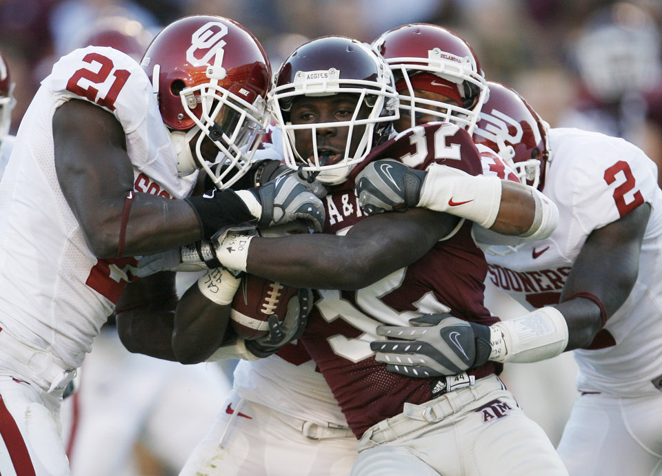 Photo - OU's J.R. Bryant (21), Jamell Fleming (32) and Brian Jackson (2) bring down Cyrus Gray (32) of Texas A&M in the first half during the college football game between the University of Oklahoma (OU) and Texas A&M University (TAMU) at Kyle Field in College Station, Texas, Saturday, Nov. 8, 2008. BY NATE BILLINGS, THE OKLAHOMAN